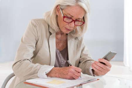 mujeres ancianas: Senior mujer ejecutiva con calendario y teléfono celular  Foto de archivo