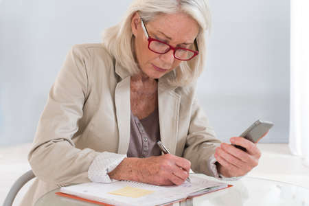 woman mature: Senior woman executive with schedule and cell phone
