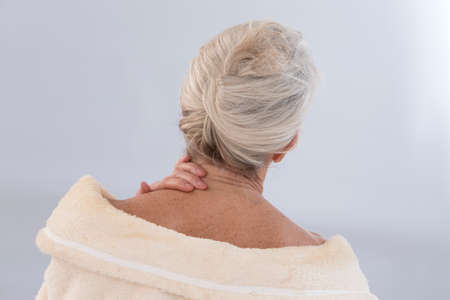 Senior Woman with neck pain, back view Stock Photo