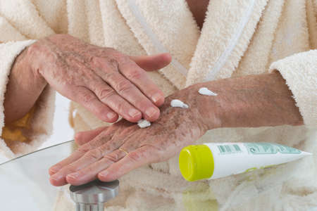 unguent: Old man applying hand cream at home