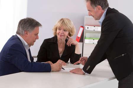 Senior paar schrijven handtekening onder contract na financiële overleg Stockfoto