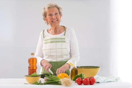 eating fruits: Happy senior woman  cooking at kitchen Stock Photo
