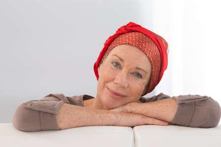 彼女の笑顔の前向きな姿勢に焦点を当てる - 化学療法後に復旧する素敵な中年の女性の肖像画