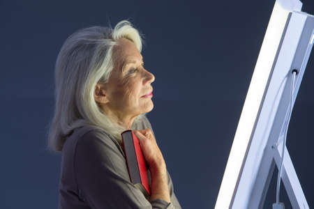 impure: Light therapy-Senior woman getting face phototherapy treatment Stock Photo