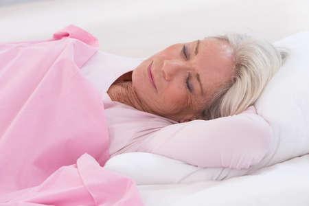 senior vrouw slapen op bed