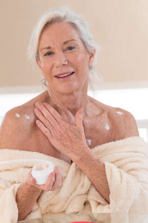 senior Woman applying moisturizer cream on her body Stock Photo