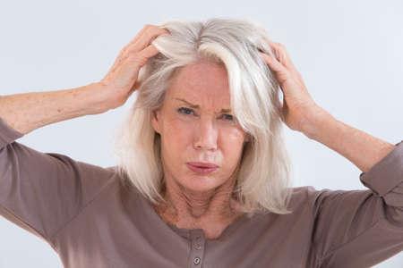 Senior vrouw woedend haar hoofd krabben