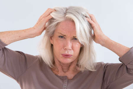 white hair: Senior woman furiously scratching her head Stock Photo