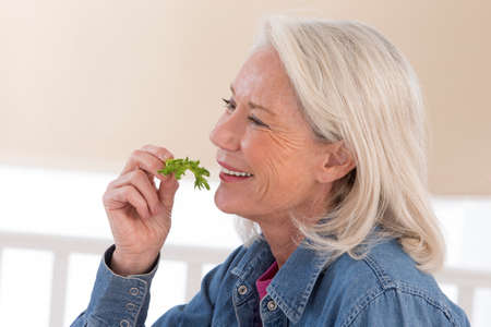 beautiful salad: Senior woman eating a healthy salad at the kitchen