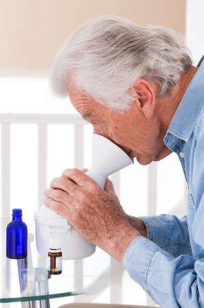 inhalation: portrait of an senior man making inhalation