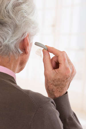 audible: profile view of a senior woman inserting a hearing aid in his hear Stock Photo