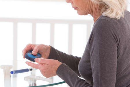 blood glucose meter: woman with test strip and blood glucose meter