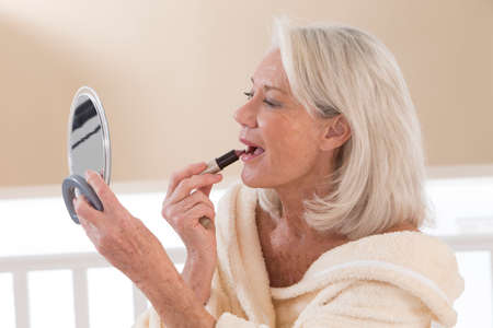 applying lipstick: Senior Woman applying lipstick while looking in her mirror Stock Photo