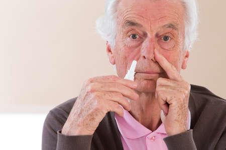 bottle nose: Senior man spraying medication in his nose