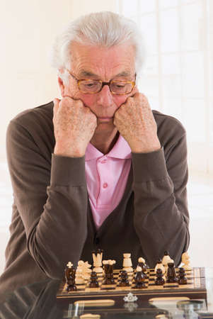 pawn adult: SGame and strategy- Senior chess player deeply concentrated on the chessboard .