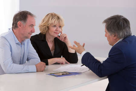 financial planning married: Senior couple meeting architect for building project Stock Photo