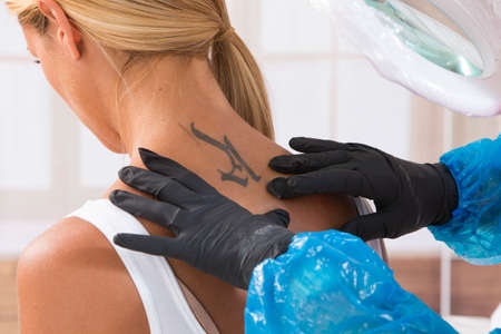 famous women: creating tatoo on a young gilrs back