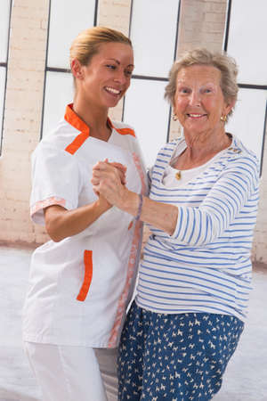 care giver: Care giver dansing with senior woman  in nursing home Stock Photo