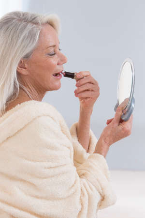 lip pencil: Senior Woman applying lipstick while looking in her mirror Stock Photo