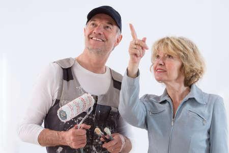 pintor: Mujer mayor que muestra a un hombre pintor donde pintar en la pared aislado sobre fondo blanco
