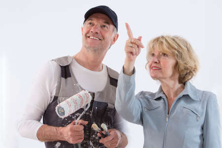 Senior woman showing to a painter man where to paint on the wall isolated on white background
