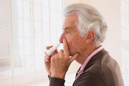 bottle nose: Senior man spraying medication in his nose