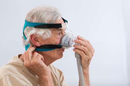 humidifier: SLEEP APNEA SYNDROME -Senior man using CPAP machine Stock Photo