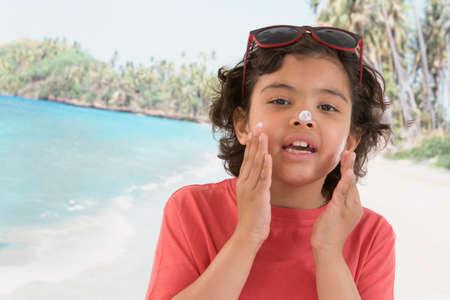 Cute Child boy  apply sunblock cream on his face on beach background