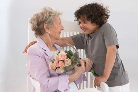 offer: Little boy offering a bouquet of flowers to his grandmother