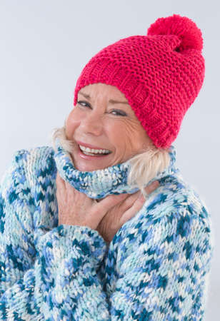 cocooning: Portrait of senior woman wearing wool sweater and hat Stock Photo