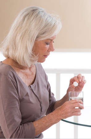 taking pill: Senior woman suffers from headache, sitting at table with pills and glass of water Stock Photo