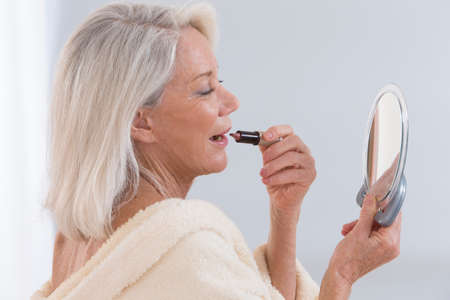 Senior Woman applying lipstick while looking in her mirror Banque d'images