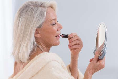 Mujer Mayor aplicar el lápiz labial mientras se mira en el espejo Foto de archivo - 45633325