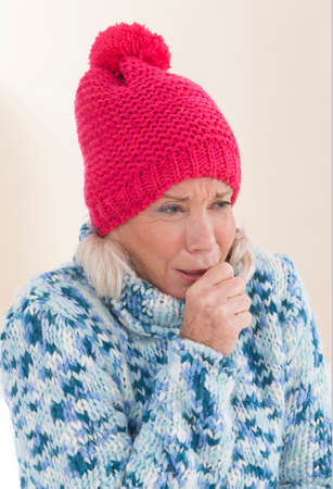 clothe: Senior woman in winter clothe, coughing Stock Photo