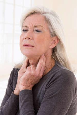 Sick woman touching her sore throat
