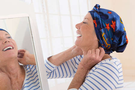 Senior woman looking at mirror and putting her scarf