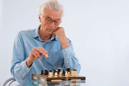 deeply: SGame and strategy- Senior chess player deeply concentrated on the chessboard .