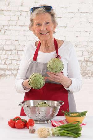 comiendo frutas: Mujer mayor feliz que cocina en la cocina