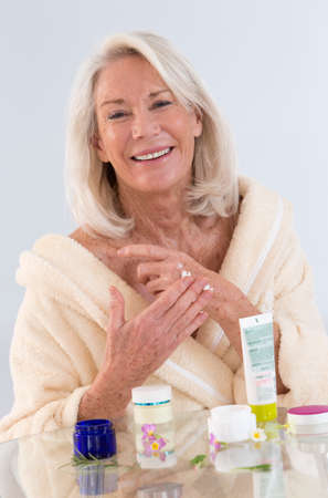 hand care: Smiling senior woman applying cream on her hands Stock Photo