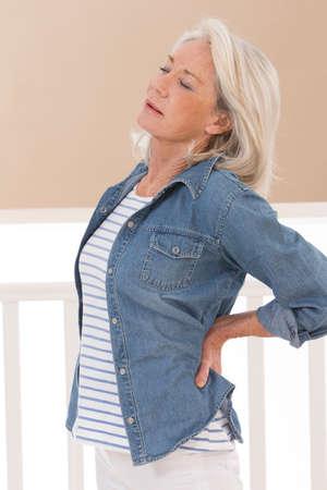 Vrouw met haar handen op haar gewonde rug  Stockfoto