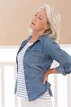senior pain: Woman holding her hands on her injured back Stock Photo