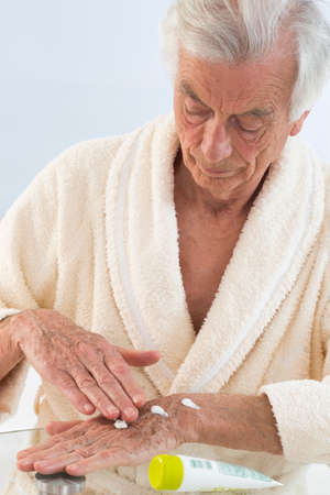 liniment: Old man applying hand cream at home