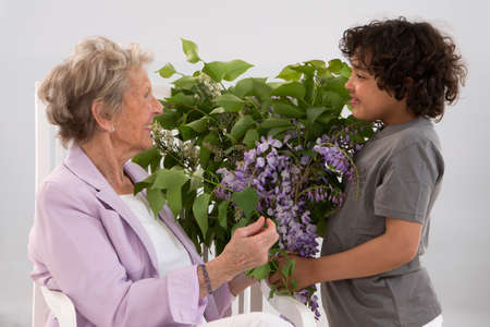 mothersday: Little boy offering a bouquet of flowers to his grandmother