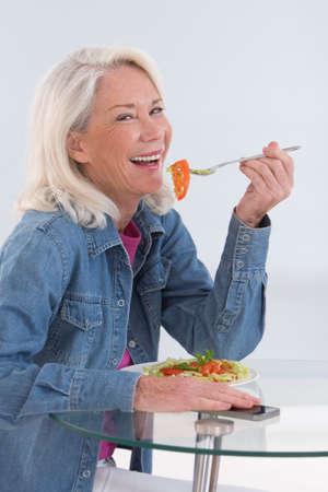 cebollas: Mujer mayor que come una ensalada saludable en la cocina Foto de archivo