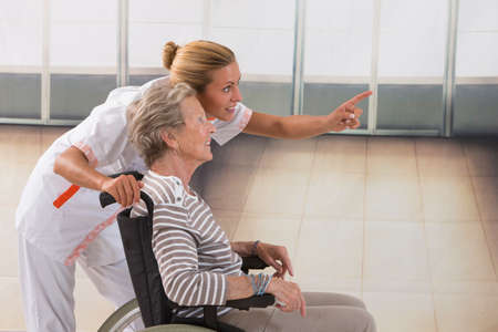 home health nurse: Elderly lady on wheelchair and her nurse Stock Photo