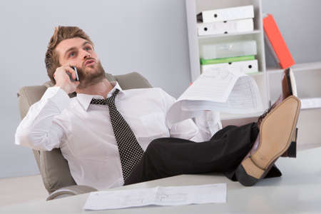 business man phone: Young businessman in office sitting with feet on desk talking on cellphone.