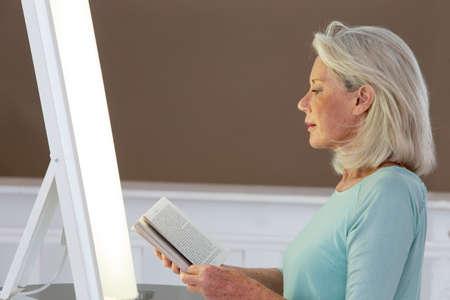 Lichttherapie-Senior vrouw krijgt gezicht fototherapie behandeling