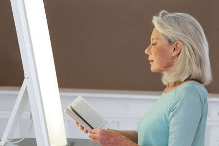 Light therapy-Senior woman getting face phototherapy treatment Stock Photo