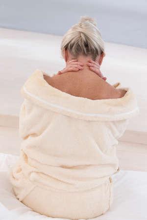 Senior Woman with neck pain, back view Standard-Bild