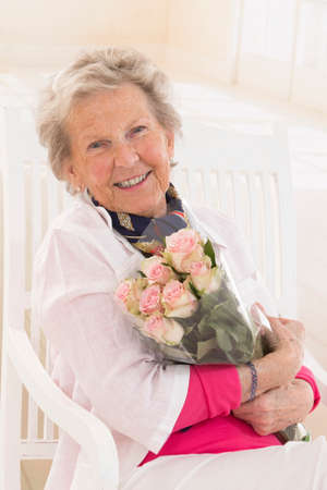 bunch of flowers: Happy attractive senior woman with a bunch of flowers Stock Photo